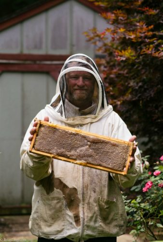 the viking in my life holding up a frame of honey